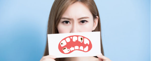 girl with sign over her mouth showing cavities