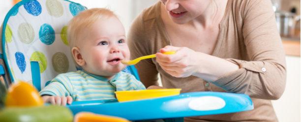 mother spoon-feeding baby