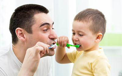 Dad Teaching His Son to Brush His Teeth