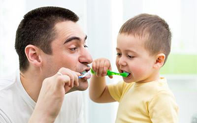 Dad Teaching His Son to Brush His Teeth